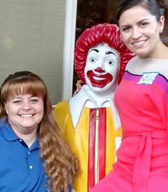 Two volunteers sit with our Ronald McDonald Bench