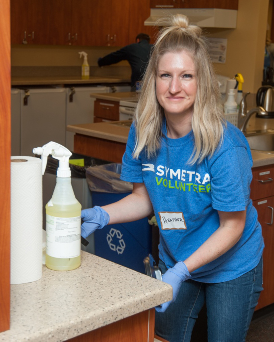 A volunteer cleans the kitchen at the Seattle House.