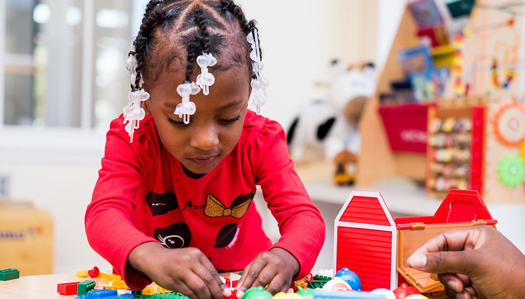 A girl plays with Legos at a Ronald McDonald House.