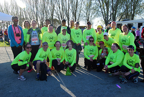 A group shot of former RMHC's running club members in matching t-shirts.