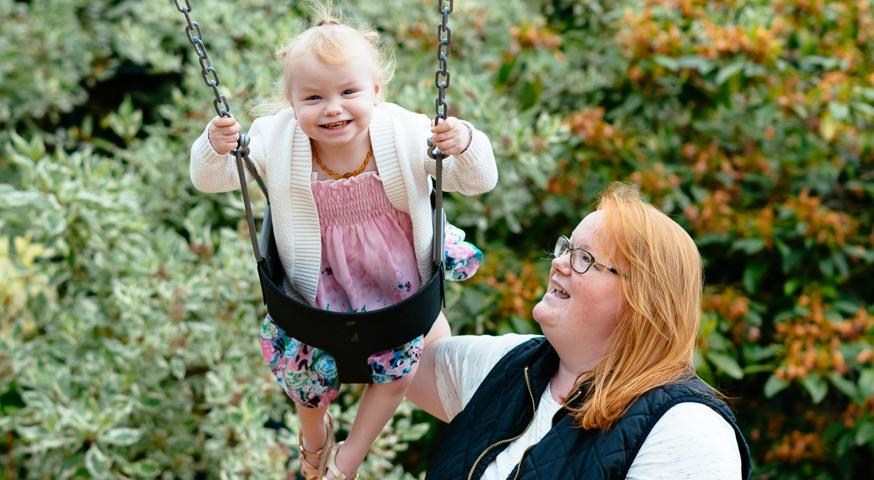 Constance, a three-year-old girl with a ponytail, plays on the swings as her mother looks on